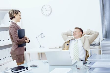Satisfied businessman sitting at desk in office, smiling and looking up to his secretary. photo