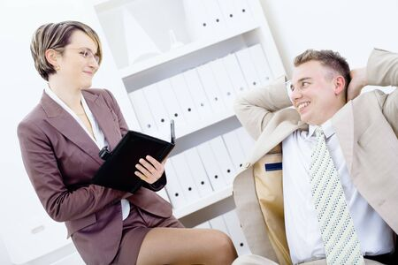 Satisfied businessman sitting at desk in office, smiling and looking up to his secretary, holding personal organizer. photo