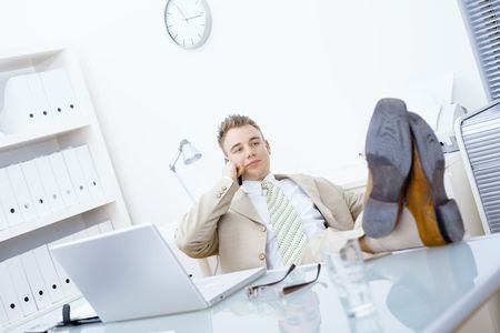 fulfilled: Satisfied businessman sitting by desk at office, feet on table, talking on mobile phone.