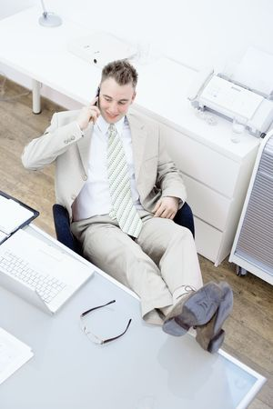 fulfilled: Satisfied businessman sitting by desk at office, feet on table, talking on mobile phone. High-angle view.