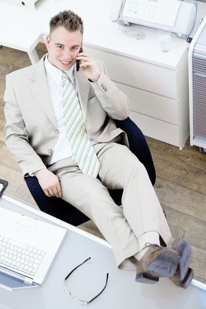 fulfilled: Satisfied businessman sitting by desk at office, feet on table, talking on mobile phone, smiling. High-angle view. Stock Photo