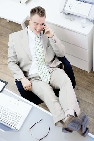 gratified: Satisfied businessman sitting by desk at office, feet on table, talking on mobile phone, smiling. High-angle view. Stock Photo