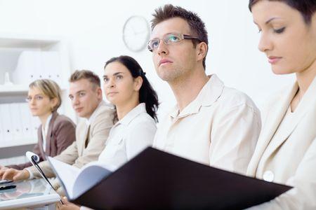 Cinco compañeros de negocio sentado en una fila de una formación de negocio y prestar atención, de cara al futuro. Atención selectiva en los hombres en el frente. Foto de archivo