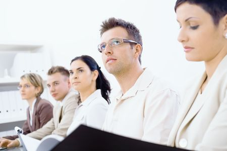 corporate image: Five businesspeople sitting in a row on a business training and paying attention, looking ahead. Selective focus placed on men in front Stock Photo