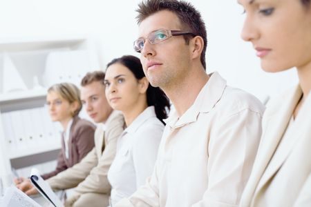 Five business colleagues sitting in a row on a business presentation and paying attention, looking ahead. Selective focus placed on men in front Stock Photo - 6338441