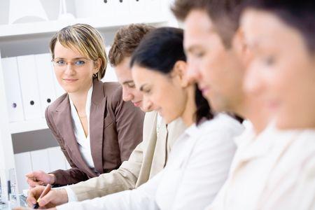 rows: Vijf collega's zitten in een rij op een zakelijke presentatie. Selectieve focus gelegd op de vrouw op de achtergrond. Stockfoto
