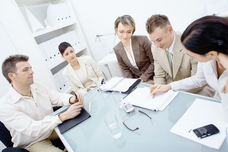 Five businesspeople sitting around table in office and having a meeting. Writing and discussing notes on paper. photo