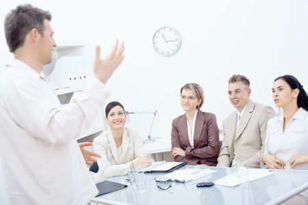 open collar: Businessman standing and explaining to four colleagues sitting around office table.