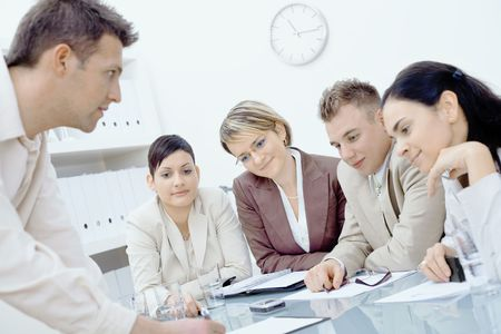 Businessman leaning on desk, explaining business plans to four colleagues sitting on the other side. Stock Photo - 6338406