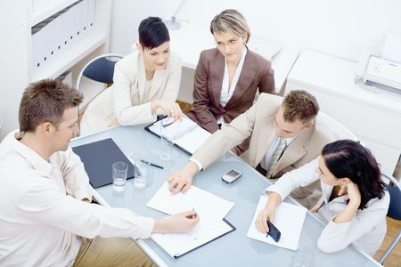 Five businesspeople sitting around table in office and having a meeting. Discussing business plans and writing notes on paper. photo