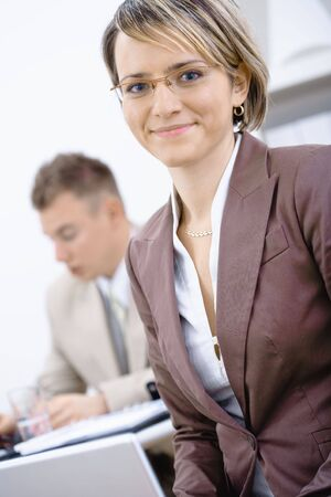 Portrait of young businesswoman in office. Businessman working in the background. photo