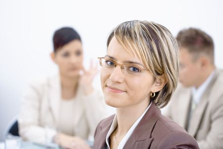 Portrait of young businesswoman in office. Business people working in background. photo