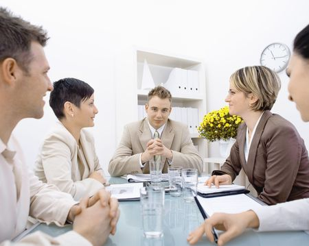businesswear: Satisfied businessman having a meeting with team at office, looking at camera, smiling.