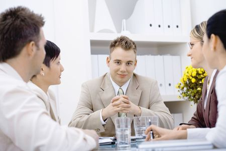 Satisfied businessman having a meeting with team at office, looking at camera, smiling. photo
