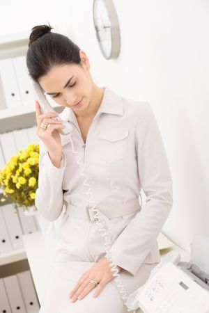 Young businesswoman wearing beige suit talking on landline phone in office, smiling. photo