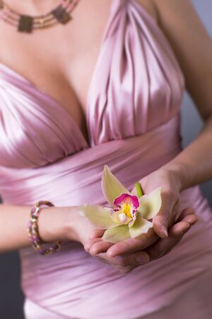 Women wearing evening dress holding a yellow and purple orchid flower in hands. Women only partially visible. Stock Photo - 6347729