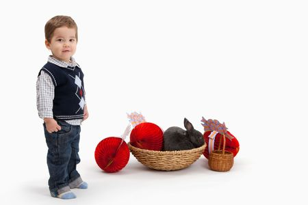 1 2 month: Little boy with Easter bunny and decoration, looking at camera, isolated on white background. Stock Photo