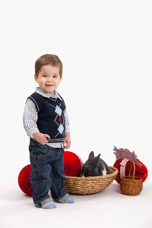 Happy little boy with Easter bunny and decoration, looking at camera, isolated on white background. photo