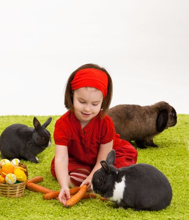 Easter image: smiling little girl with Easter bunnies on green carpet. Stock Photo - 6338548