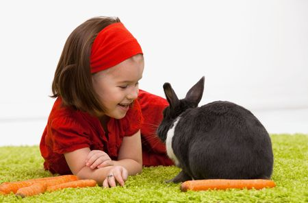Easter image: smiling little girl with Easter bunny on green carpet. photo