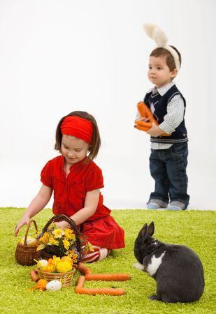 3 4 length: Easter image: smiling little girl with Easter bunny on green carpet. Stock Photo