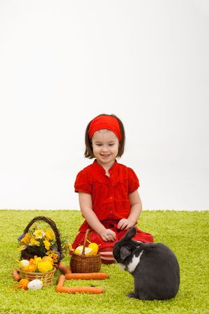 Easter image: smiling little girl with Easter bunny on green carpet. Stock Photo - 6338545