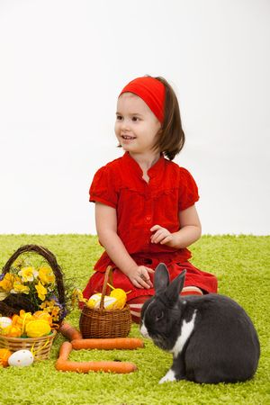 Easter image: smiling little girl with Easter bunny on green carpet. Stock Photo - 6338542