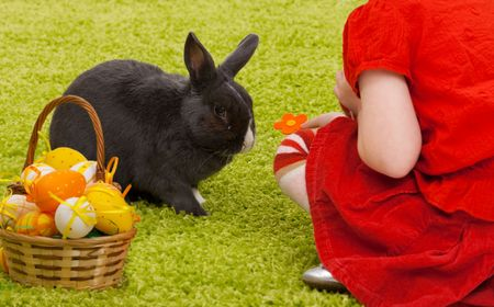 Easter image:  little girl playing with Easter bunny on green carpet. photo