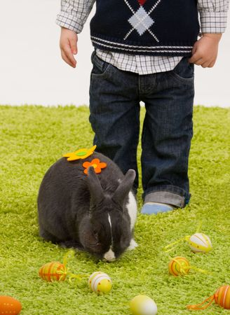 Easter image:  little boy playing with Easter bunny on green carpet. photo