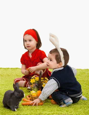 Little children playing with Easter bunny on green carpet. Focus placed on bpy in front, girl is out of focus. photo
