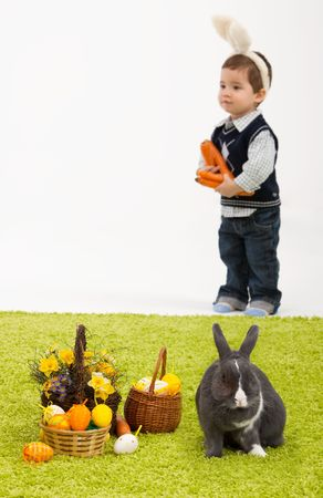 Little children playing with Easter bunny on green carpet. Focus placed on easter bunny in front, boy is out of focus. photo