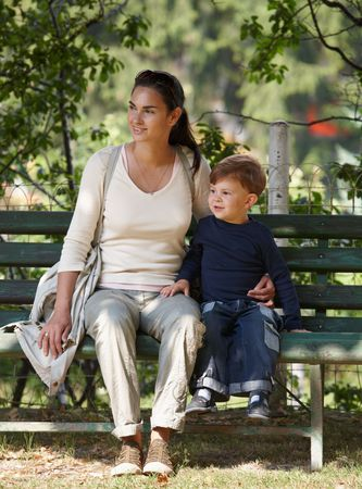 Mother and little son sitting together on bench in park, cuddling, smiling. Stock Photo - 6338549