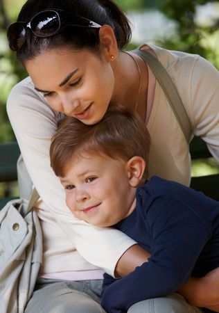 mom and son: Mother and affectionate child cuddling together in park, smiling.