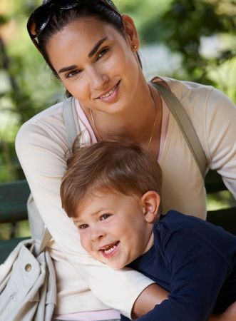 age 5: Happy mother and little boy cuddling together in park, smiling.