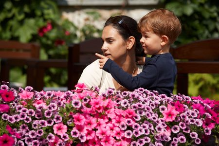 Three years old son explaining to mother outdoor in spring garden. Stock Photo - 6338640