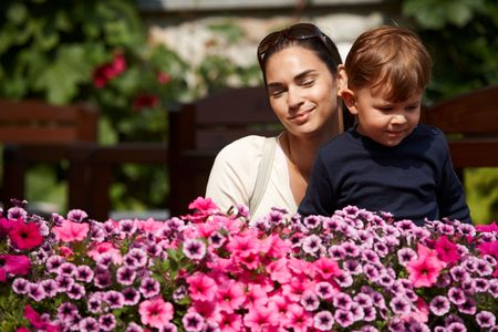 Three years old kid and mother together outdoor in spring garden. photo