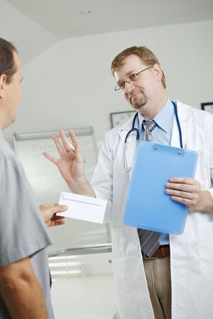 Medical office - patient bribing doctor, giving money in envelope, doctor rejecting it. photo