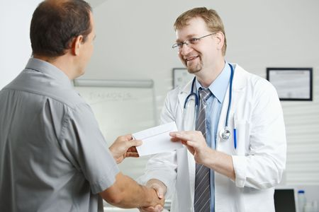 Medical office - patient bribing doctor, giving money in envelope. photo