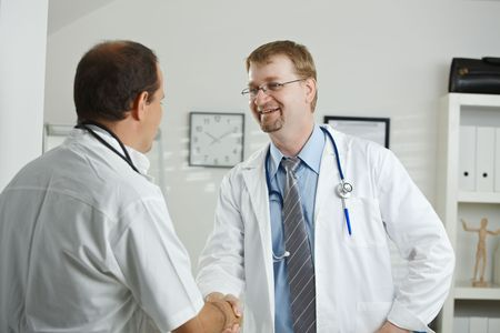 Medical office - middle-aged male doctors having consultation at office, shaking hands. photo