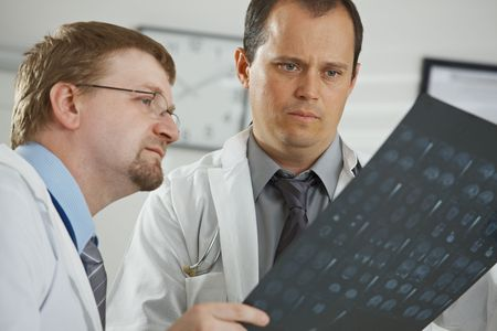 Medical office - middle-aged male doctors having consultation over computer tomograph scan. photo