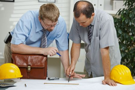 Architects working at office - planning and looking at blueprint on desk.  photo
