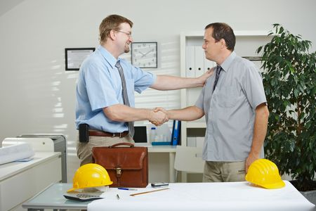 intelligent partnership: Architects working at office - shaking hands, smiling. Stock Photo