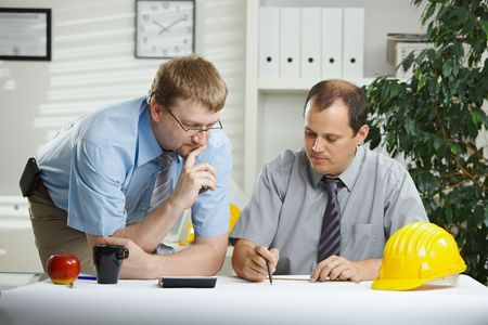 specialists: Architects working at office - planning and talking over blueprint on desk.  Stock Photo