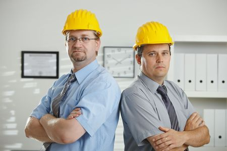 Architects in hardhats posing for teamphoto at office.  photo