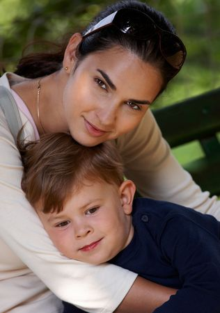 Mother and son cuddling together outdoor, smiling. photo