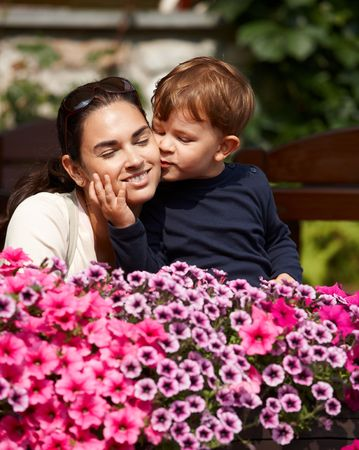 Three years old kid kissing happy mother outdoor in spring garden, smiling. photo