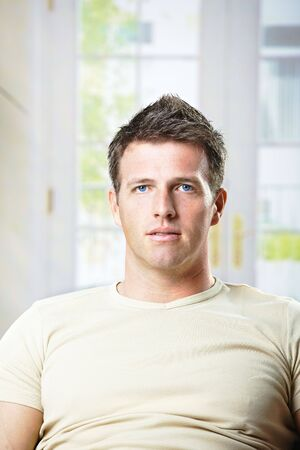 Portrait of mid-adult man sitting at home in front of window in causal t-shirt. Stock Photo - 6338643