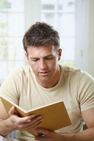 Mid-adult man reading at home sitting on couch with book handheld. photo