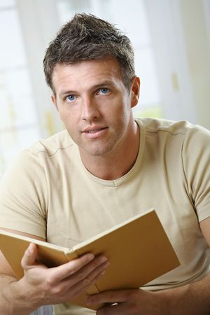 Mid-adult man at home sitting on couch with book handheld looking up at camera. Stock Photo - 6338762