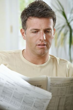 Handsome man reading newspaper at home in casual wear. Stock Photo - 6338815